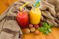 Smoothies апельсина и арбуза с lichee на скатерти Стоковое Фото