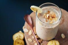 Smoothies банана плодоовощ с молоком, миндалиной, шелушатся Стоковые Изображения