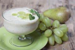 Smoothies груш и зеленых виноградин с югуртом в стеклянном шаре Стоковые Фото