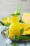 Smoothies желтого арбуза с листьями льда и мяты в стекле стоковое изображение