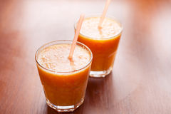 Smoothies лимона и апельсина на таблице с кусками лимона и апельсина в чашках стекла с трубками Стоковая Фотография RF