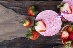 Smoothies клубники и клубника приносить для для milkshake на деревянной предпосылке от взгляд сверху стоковые фото