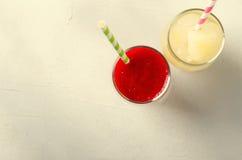 Smoothies клубники и лимонад льда с трубками коктеиля в стеклах, на белой предпосылке Стоковое фото RF