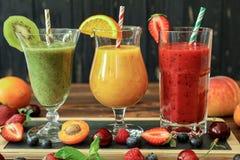 3 smoothies от различных плодоовощей и ягод как киви, апельсин, персик, абрикос, вишня, клубника, поленика Стоковое фото RF