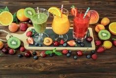 3 smoothies от различных плодоовощей и ягод как киви, апельсин, персик, абрикос, вишня, клубника, поленика Стоковая Фотография