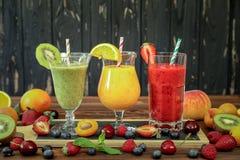 3 smoothies от различных плодоовощей и ягод как киви, апельсин, персик, абрикос, вишня, клубника, поленика Стоковое Фото