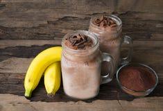 Smoothies банана и шоколада доят положили стекло на деревянную предпосылку стоковое изображение