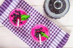 Smoothies av den svarta vinbäret i glass exponeringsglas med sugrör på en vit trätabell Top beskådar Royaltyfria Foton