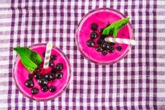Smoothies av den svarta vinbäret i glass exponeringsglas med sugrör på en vit trätabell Top beskådar Royaltyfri Bild