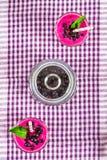 Smoothies av den svarta vinbäret i glass exponeringsglas med sugrör på en vit trätabell Top beskådar Royaltyfri Fotografi