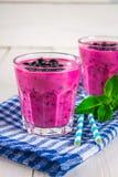 Smoothies av den svarta vinbäret i glass exponeringsglas med sugrör på en whi Arkivbilder