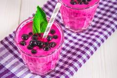 Smoothies av den svarta vinbäret i glass exponeringsglas med sugrör på en whi Royaltyfria Foton