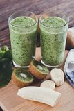Smoothies from banana, spinach and kiwi on a wooden table Royalty Free Stock Image