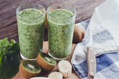 Smoothies from banana, spinach and kiwi on a wooden table Royalty Free Stock Photo