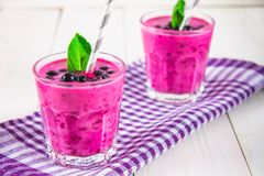 Smoothies of black currant in glass glasses with straws on a whi. Te wooden table Royalty Free Stock Images