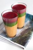 Smoothies coloridos de la fruta en el periódico Imágenes de archivo libres de regalías