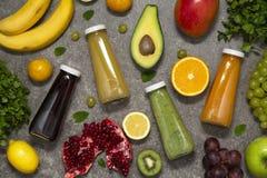 Smoothies coloridos en botellas con la fruta y verdura tropical fresca en el fondo concreto, visión superior Endecha plana fotos de archivo libres de regalías