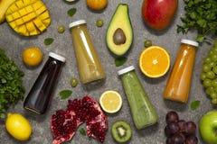 Smoothies coloridos en botellas con la fruta y verdura tropical fresca en el fondo concreto, visión superior Endecha plana foto de archivo libre de regalías