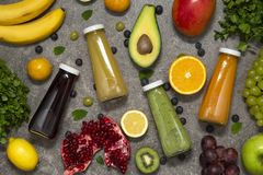 Smoothies coloridos en botellas con la fruta y verdura tropical fresca en el fondo concreto, visión superior Endecha plana foto de archivo