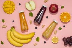 Smoothies coloridos en botellas con las frutas frescas en fondo rosado Endecha plana, visión superior imágenes de archivo libres de regalías