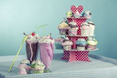 Smoothies and cupcakes. Are smoothies and cupcakes with cream with the style of the sixties royalty free stock photography
