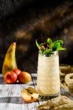 Smoothies délicieux des pommes et des poires dans un beau verre décoré de la menthe sur un fond en bois clair Photographie stock
