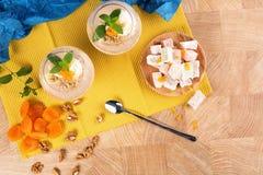 Smoothies de banane d'été dans des verres énormes avec le plaisir turc, les abricots secs et les noix sur le fond multicolore Photographie stock