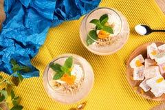 Smoothies de banane d'été dans des verres énormes avec le plaisir turc, les abricots secs et les noix sur le fond multicolore Image stock