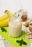 Smoothies de banane dans un pot en verre sur un fond blanc Image stock
