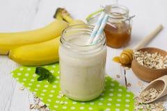 Smoothies de banane dans un pot en verre sur un fond blanc Images libres de droits