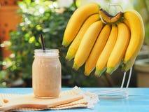 Smoothies de banane en verre avec les bananes fraîches accrochant sur le cintre Photos stock
