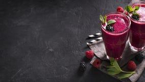Smoothies de Blackberry y de la frambuesa en vidrio con la hoja de la menta y r fotografía de archivo