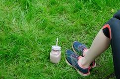 Smoothies de fraise et jambes femelles dans des espadrilles contre un backg Image stock
