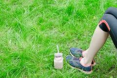 Smoothies de fraise et jambes femelles dans des espadrilles sur l'herbe verte Photos libres de droits