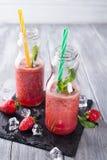 Smoothies de la fresa en botellas fotos de archivo
