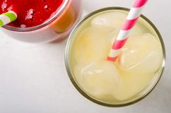 Smoothies de la fresa y limonada del hielo con los tubos del cóctel en vidrios, en el fondo blanco Fotografía de archivo libre de regalías