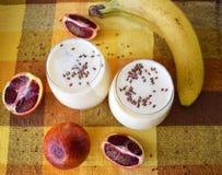 Smoothies de la fruta en vidrios en una tabla con un mantel amarillo Fotografía de archivo libre de regalías