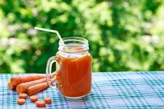Smoothies de las zanahorias en un tarro y pedazos de zanahorias frescas Foto de archivo libre de regalías