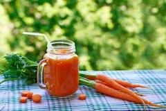 Smoothies de las zanahorias en un tarro y zanahorias frescas Imágenes de archivo libres de regalías