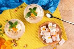Smoothies del plátano del verano en vidrios enormes con placer turco, albaricoques secados y nueces en fondo multicolor Imagen de archivo libre de regalías