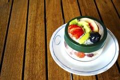 Smoothies del postre con las frutas en una placa blanca Imagenes de archivo