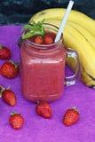 Smoothies deliciosos con las fresas y el plátano imagen de archivo