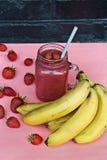 Smoothies deliciosos con las fresas y el plátano Colores brillantes del verano imagen de archivo