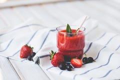Smoothies der Schwarzen Johannisbeere und der Erdbeeren mit Jogurt auf einem weißen Holztisch Lizenzfreie Stockfotografie