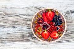 Smoothies för Acai frukostsuperfoods bowlar med chiafrö, bipollen, gojibärtoppningar och jordnötsmör overhead arkivfoto