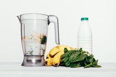 Smoothies in a food processor. From a banana, spinach and milk on a white background Royalty Free Stock Photography