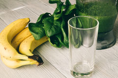 Smoothies in the food processor, empty glass, banana and spinach Royalty Free Stock Photos