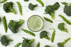 Smoothies frescos del bróculi crudo y de los guisantes de olor verdes en una tabla de madera blanca imágenes de archivo libres de regalías