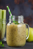 Smoothies of kiwi, celery and apple in a glass jar stock image