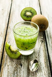 Smoothies of kiwi. On the wooden table stock photography